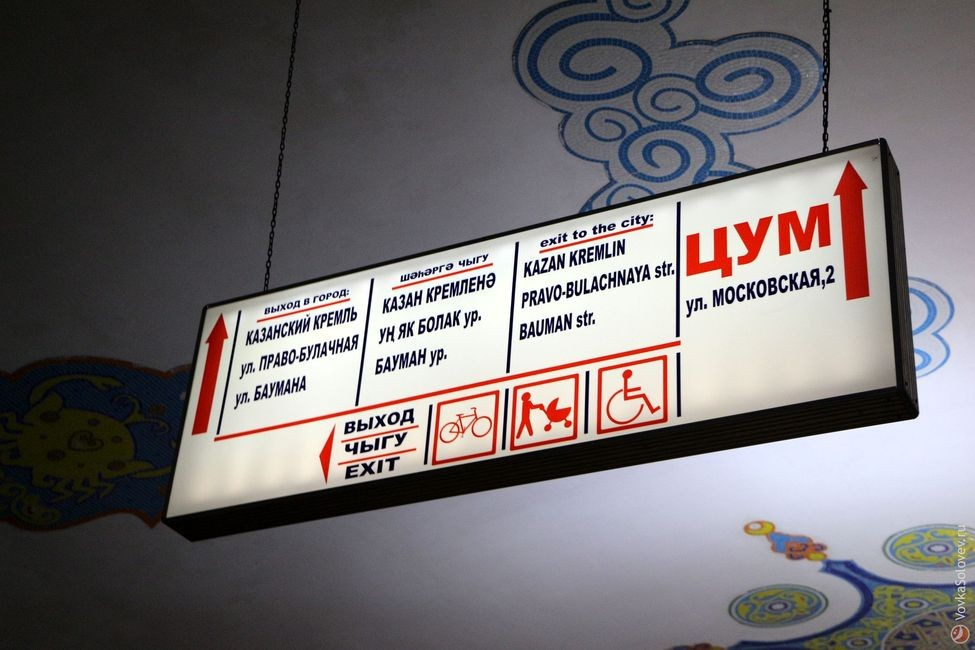 Потолочный указатель перед лестницей на выход на трех языках. Пиктограммы очень странные и из разных наборов: у велосипеда нет вилки руля, коляска как пэкман на колёсиках.